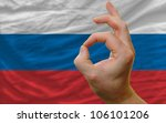 man showing excellence or ok gesture in front of complete wavy russia national flag symbolizing best quality, positivity and success - stock photo