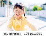 happy little girl wearing... | Shutterstock . vector #1061013092