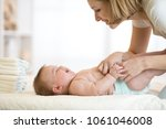 mom changing a diaper on... | Shutterstock . vector #1061046008
