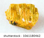 Small photo of macro shooting of natural mineral rock specimen - raw native orpiment stone on white marble background from Yakutia, Russia