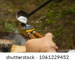 Small photo of bullet making round projectile for historical weapons muskets liquid metal is poured is formed in hand form against the background of a bonfire, a classic recipe casting projectile reconstruction