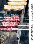 Small photo of Arrosticini and bread on the grill, Abruzzi skewers of sheep cooked on the grate and on a special brazier.