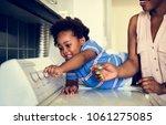 african descent kid helping mom ... | Shutterstock . vector #1061275085