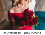 Stock photo cropped shot of man embracing girlfriend in red dress holding beautiful roses 1061409245