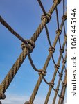 Small photo of Ropes, pulley, shroud - parts of an old ship, sailboat. Blue sky in the background.