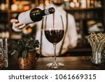 Stock photo bartender pouring red wine from a bottle in a wine glass selective point of view on a wine glass 1061669315