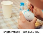 Small photo of A little boy holding a brush in his hands and decorating a cup. And he draws a heart with a blue paint. Drawing lesson. Drawing process closeup.