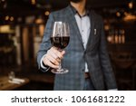a young man holding a glass of... | Shutterstock . vector #1061681222