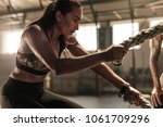 fit woman using battle ropes... | Shutterstock . vector #1061709296