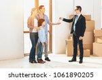 realtor in suit is giving keys... | Shutterstock . vector #1061890205