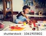 black kid enjoying his painting | Shutterstock . vector #1061905802