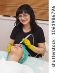 Small photo of The cosmetologist makes the apparatus a procedure of Microcurrent therapy of a beautiful, young woman in a beauty salon. Cosmetology and professional skin care.