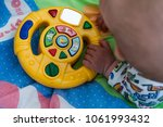 the child is playing with a toy.... | Shutterstock . vector #1061993432