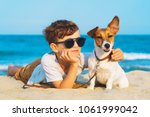 Stock photo happy year old boy hugging his dog breed jack russell terrier at the seashore against a blue sky 1061999042