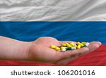 man holding capsules in front of complete wavy national flag of russia symbolizing health, medicine, cure, vitamins and healthy life - stock photo