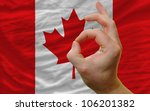 man showing excellence or ok gesture in front of complete wavy canada national flag of  symbolizing best quality, positivity and success - stock photo