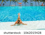 woman at the swimming pool at... | Shutterstock . vector #1062015428