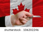man stretching out credit card to buy goods in front of complete wavy national flag of canada - stock photo