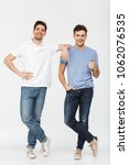 Small photo of Full length photo of two handsome men pals 30s wearing casual t-shirt and jeans smiling and posing together on camera with thumb up isolated over white background
