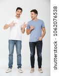 Full length photo of two handsome men 30s wearing casual t-shirt and jeans smiling and gesturing fingers on each other isolated over white background