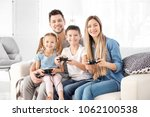 happy family playing video... | Shutterstock . vector #1062100538