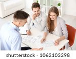 real estate agent showing plan... | Shutterstock . vector #1062103298