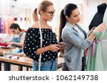 Small photo of Three girls at garment factory. They are happy and fashionable. They are looking at desing of new dress.