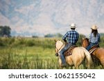 Stock photo a couple horseback riding from behind overlooking wide open field and mountains of utah wilderness 1062155042