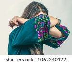 Small photo of Sad emotional senior woman with long gray hair in a turquoise dress with a pattern standing with closed face on a white background of wall.
