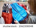 buyer woman chooses waistcoat... | Shutterstock . vector #1062338348