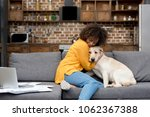 Stock photo beautiful young woman working at home and cuddling with her dog 1062367388