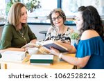 group of women sitting around a ... | Shutterstock . vector #1062528212