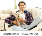 Stock photo handsome guy with a dog sitting in a large armchair 1062721055