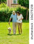 Stock photo happy couple walking golden retriever dog on park lawn smiling 106275158