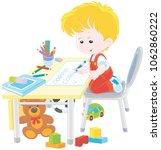 little boy doing his homework... | Shutterstock .eps vector #1062860222