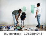 black family painting house wall | Shutterstock . vector #1062884045