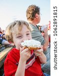 young boy eating a whipped... | Shutterstock . vector #1062891815