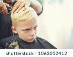 cute young blonde boy getting... | Shutterstock . vector #1063012412