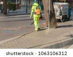 landscaper worker cleaning foot ... | Shutterstock . vector #1063106312