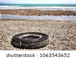 abandoned car tire on a beach... | Shutterstock . vector #1063543652