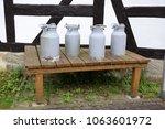 milk churns at a farm house | Shutterstock . vector #1063601972