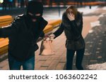 Small photo of Thief Dangerous man or masked robber with knife attacking shoulder bag. Robber or thief holding knife burglarize to steal the money wallet in woman's bag, while sitting at restaurant and don't careful