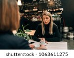 two girl friends in a cafe... | Shutterstock . vector #1063611275
