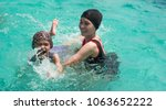 Small photo of Blurry mother tainting daughter swimming in swimming pool on summer holiday.