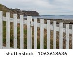 A white picket fence in the foreground with grass on the far side. The ocean and cliffside is in the background. The sky is blue with some clouds.  There