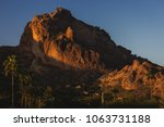 Popular Camelback Mountain with patches of sunlight cast upon the peak at sunrise, Paradise Valley, Arizona