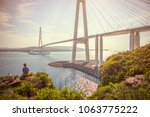 Girl  looks at  the cruise liner passing under Russky Bridge
