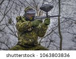 Small photo of Paintball player takes aim, hides and shooting. Man wearing protective equipment