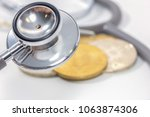 stethoscope and gold bitcoin on ... | Shutterstock . vector #1063874306