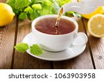 tea pouring from teapot into a... | Shutterstock . vector #1063903958